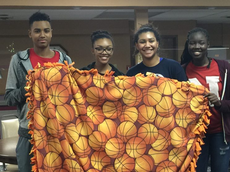 Lead Up students show off their finished blanket to be donated to Project Linus.